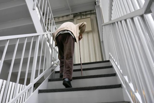 階段を上がる老人